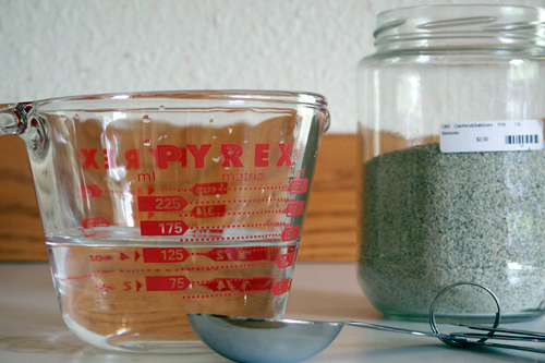 Ready to measure bentonite with 150 ml water in a measuring cup, bentonite powder in a jar, and measuring spoons.
