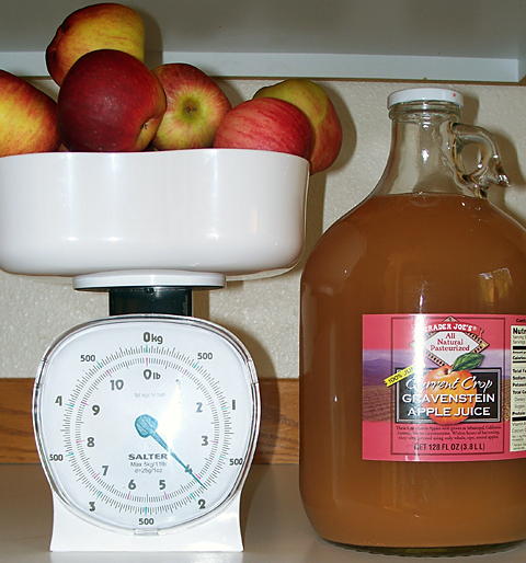 Apples on a kitchen scale reading just over 4 lb and Trader Joe's Gravenstein apple juice. The main ingredients of my apple wine.